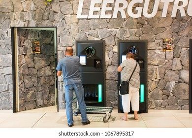 MANNHEIM, GERMANY - AUGUST 28 : German people put and return empty bottle into Reverse Vending Machine and receive money from machinery at supermarket on August 28, 2017 in Mannheim, Germany