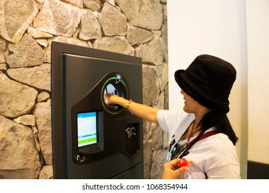 MANNHEIM, GERMANY - AUGUST 28 : Thai women test using put and return empty bottle into Reverse Vending Machine and receive money from machinery at supermarket on August 28, 2017 in Mannheim, Germany