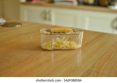 Mannheim, Germany - August 3, 2019 : Grated parmesan inside the plastic grater; the rind of cheese is shown on top