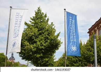 Mannheim, Germany - July 2019: Blue and white flags with emblem of University of Mannheim blowing in the wind