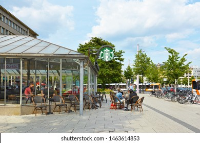 Mannheim, Germany - July 2019: Chain of cafe and shop called 'Starbucks' with glass windows and outdoor tables on a sunny summer day near city center of Mannheim