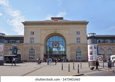Mannheim, Germany - July 2019: Front view of facade of Mannheim central railway station in old historical building with travelers passing by on summer day