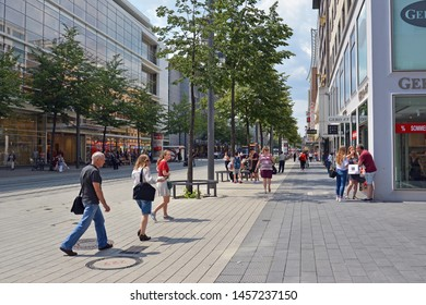 Mannheim, Germany - July 2019: People walking through city center of Mannheim with various shops on warm summer day