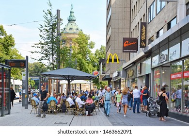 Mannheim, Germany - July 2019: People walking through city center of Mannheim with various shops and outdoor cafes on warm summer day