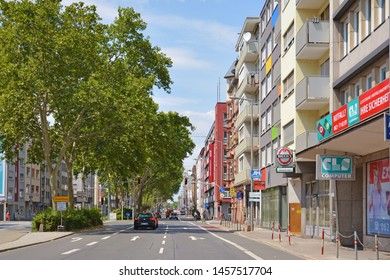 Mannheim, Germany, July 2019: Road and side street with cars and small shops in city of Mannheim