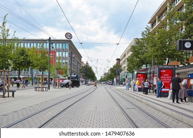 Mannheim, Germany - July 2019: Streetcar tracks leading through city center of Mannheim with various shops and people on warm summer day