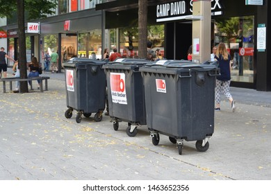 Mannheim, Germany - July 2019: Three big black garbage bins on wheels belonging to a shop standing in the city center of Mannheim