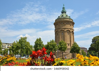 Mannheim, Germany - July 2019:  Water Tour called 'Wasserturm', landmark of German city Mannheim in small public park with colorful flowers on summer day