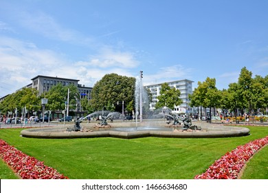 Mannheim, Germany - July 2019: Water fountains with mermen and fish spraying water in the city center of Mannheim on square called 'Friedrichsplatz' in front of water tower