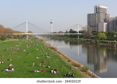 MANNHEIM, GERMANY - MAR 30, 2014: a sun-seeking crowd is relaxing at the waterfront grassland of Neckar river, enjoying the first warm and pleasant weekend of spring season