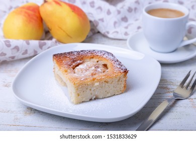 Mannik (Semolina pie) with pear and canella. In the background is a cup of coffee and fresh pears. Traditional Russian cuisine. Close-up, selective focus.