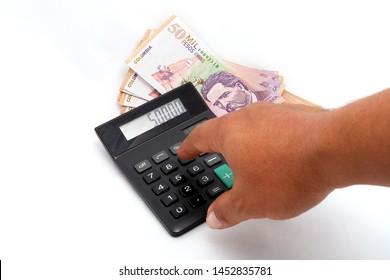 Mano, billetes y calculadora foto