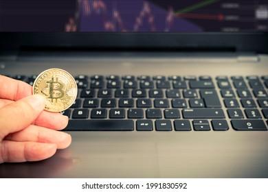 mano che tiene una moneta Bitcoin dorata su un computer portatile per analizzare il mercato delle criptovalute. Criptovaluta BTC. Valuta digitale.
