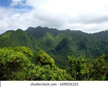 Manoa Valley and Mount Olympus, Waahila, peak more than 2,300 feet above sea level covered in a lush green forest and blue skies above.
