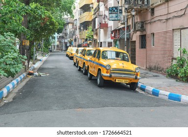 Manoharpukur, Kolkata, 5/5/2020: An empty city street with several yellow ambassador taxis parked at roadside. Nearby shops are closed and there is no people in street. During lockdown in Kolkata.