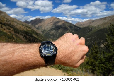 Mans arm with Sportswatch showing altitude with altimeter in the mountains while hiking and climbing with purposely blurred mountain background