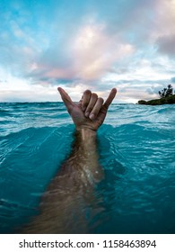 Man's Arm Underwater With Hand Above with Shaka Hand Gesture in Clear Blue Water and Colorful Evening Sky in Tropical Island Paradise Maui Hawaii