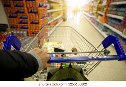 A man's arms pushing a shopping trolley full of groceries along a supermarket aisle.