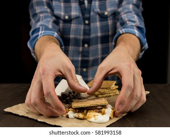 Mans Arms Reach Out for Smore with toasted marshmallows