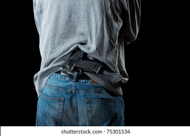 Man`s back with gun tucked in pants. Isolated on white background.