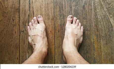 Man's bare feet on a natural wood floor