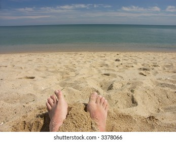 Man's bare feet protruding from sand on the beach facing the sea