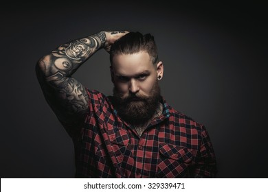 Mans with beard and tattoes on arms holding his head. Isolated on grey background.