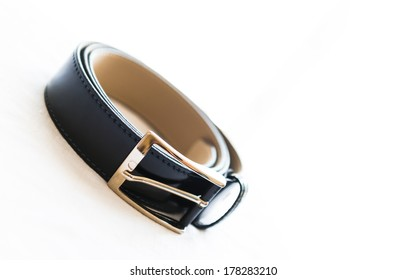 a man's black leather belt, isolated over white