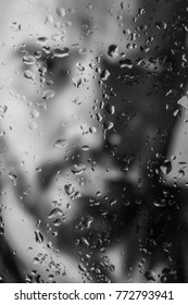 a man's blur portrait behind of glass with water drops on it