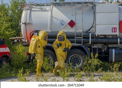 Mans with briefcase in protective hazmat suit.
