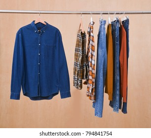 Man's cotton plaid shirt,jeans ,shirt,sweater,  hanging on wooden background