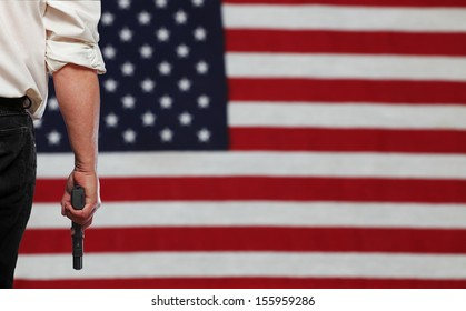 Man's in dark trousers & white shirt holding automatic pistol to one side with full view of out of focus US flag in background