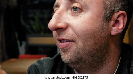 Man's emotional close portrait with big expressive eyes significant nose and small stubble beard. Dialog friendly conversation scene.