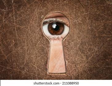 Man's eye looking through a keyhole antique door closeup