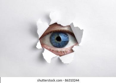Mans eye peeking through a hole in white paper
