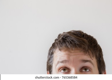 Man's eyes looking up on the gray background. Empty place for a text or object.