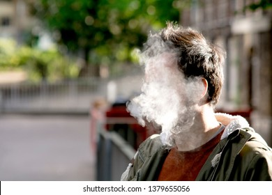 A man's face completely covered by thick cigarette smoke