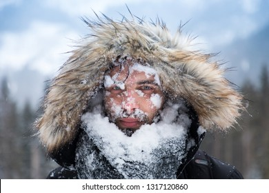 Man's face covered with snow against the backdrop of winter mountains