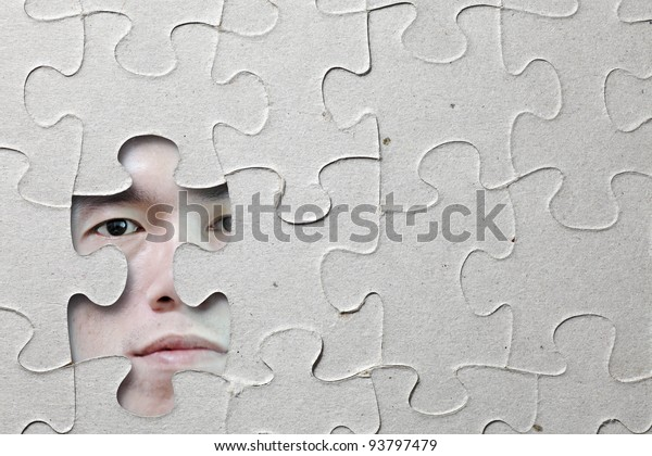 A man's face peering out from the missing pieces on the surface of a grungy paper jigsaw puzzle.