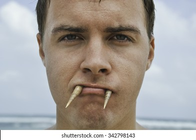 The man's face that holds the mouth two sharp shells imitating walrus tusks