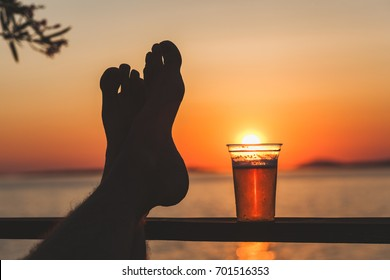 Man's feet and a beer cup with setting sun in the background