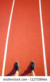 Man's feet in black sneakers stay on red running track in stadium. Concept run. Love sport