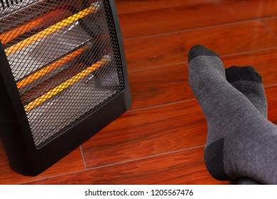 mans feet in front of an electric heater at home