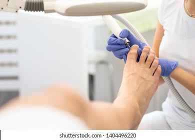 Man's feet hardware pedicure using electric machine. Patient on medical pedicure procedure. Concept about body care, spa treatment