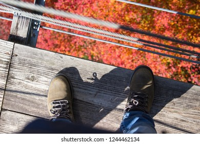 Man's feet and legs on wooden bridge over top view for sight seeing. in during autumn leaves season