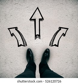 Man's feet on concrete background with drawn arrows. Different direction concept