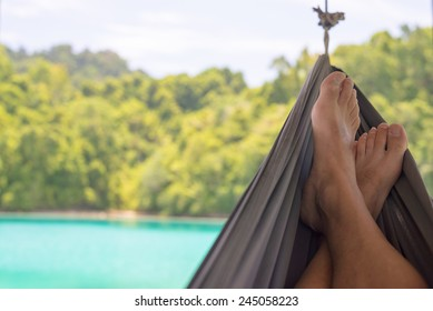 Man's feet on the hammock in the remote Togean Islands, Central Sulawesi, Indonesia.
