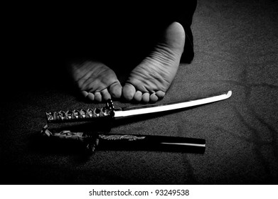 Man`s feet and ritual sword in black and white
