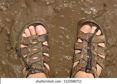 Man's feet, in sandals, in the mud.