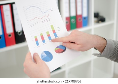 Man's finger showing business graphs at the office